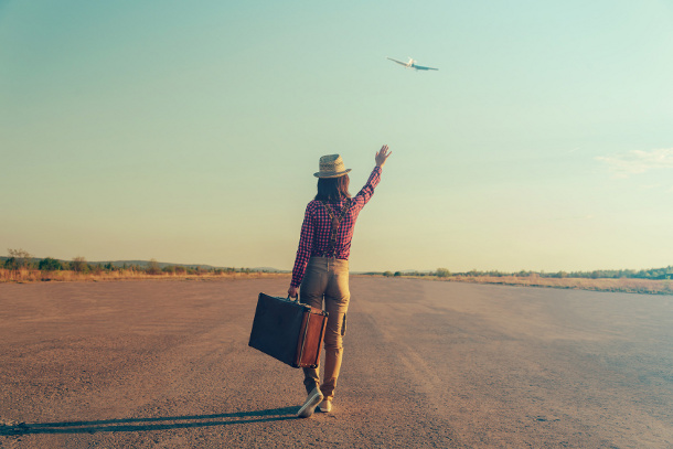 Traveler woman with vintage suitcase waves her hand to airplane, rear view, theme of travel. With vintage filter